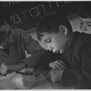 Young Jewish boys being taught by a female teacher.
