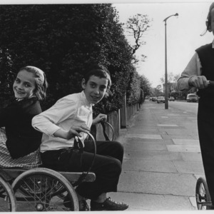Three Jewish children on the street with a scooter and a home-made go cart.